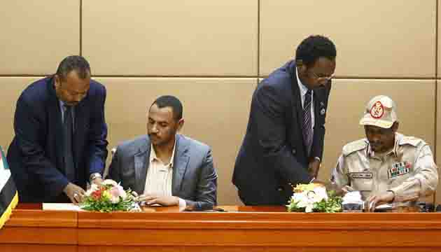 General Mohamed Hamdan Daglo, right, Sudan's deputy head of the Transitional Military Council, and protest leader Ahmed Rabie sign the constitutional declaration at a ceremony attended by African Union and Ethiopian mediators in the capital Khartoum on August 4, 2019 AFP